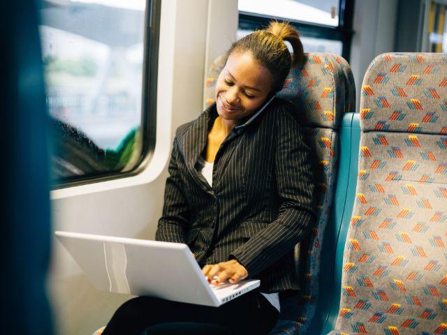 Frau mit Laptop in Bus, Foto: Peter Bernik / Shutterstock.com (Symbolbild)