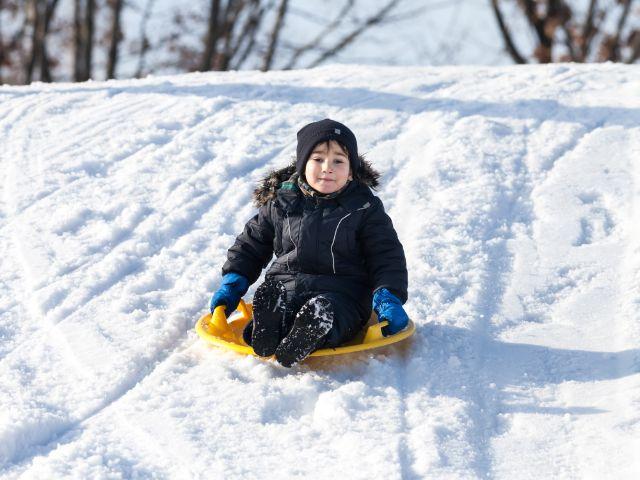 Kind rodelt auf Plastikscheibe, Foto: Drop of Light / Shutterstock.com