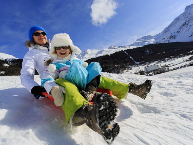 Mutter rodelt mit Kind, Foto: gorillaimages / Shutterstock.com