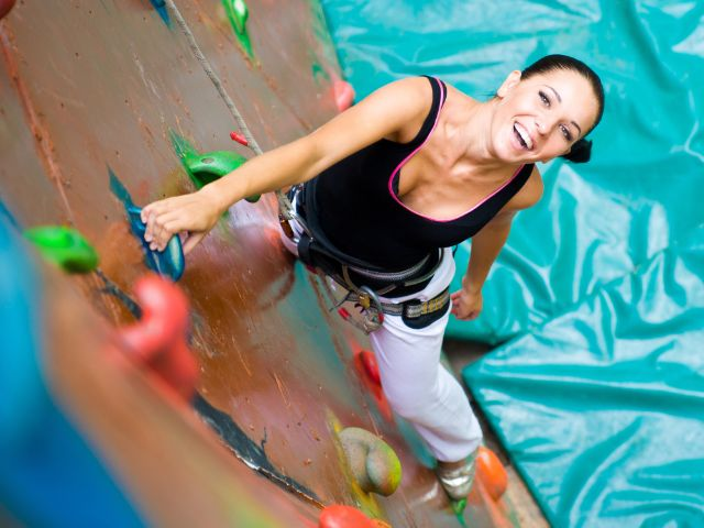 Sicht auf lachende Frau an Kletterwand von oben
