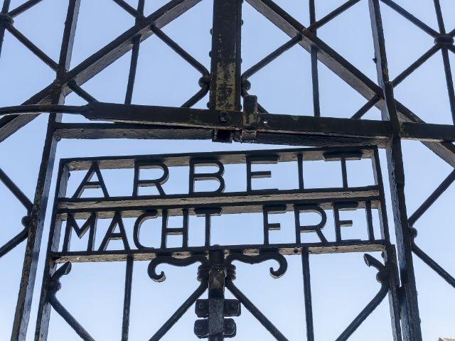 """Eingangsportal der KZ Gedenkstätte Dachau mit den Worten """"Arbeit macht frei"""", Foto: K3S / Shutterstock.com"""