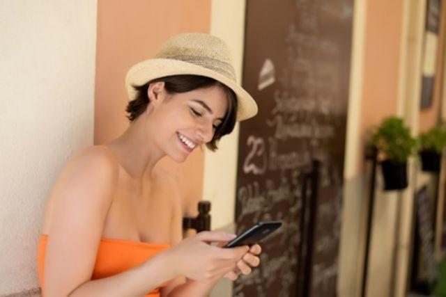 Frau mit Smartphone in Straßencafé, Foto: Fotolia