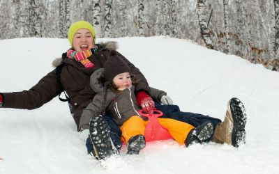 Mutter rodelt mit Kind
