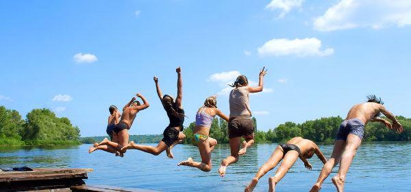 Kinder springen in See.