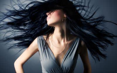 Frau schüttelt ihre langen schwarzen Haare