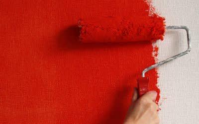 Hand mit Malerrolle streicht Wand rot