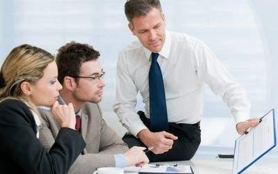 Mann zeigt zwei Kollegen eine Statistik