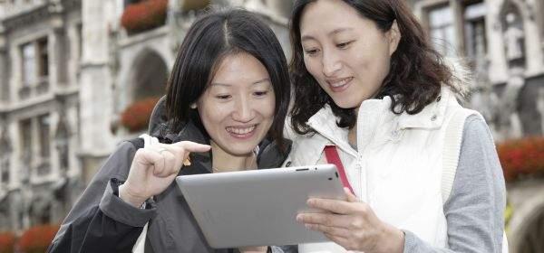 M-WLAN Marienplatz: Zwei asiatische Frauen mit Tablet vor dem Neuen Rathaus