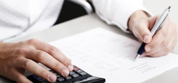 Mann rechnet mit Taschenrechner; Steuererklärung